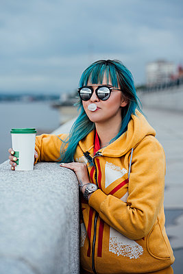 Portrait of young woman with dyed blue hair wearing mirrored sunglasses and fashionable hooded jacket - p300m2062974 by Vasily Pindyurin