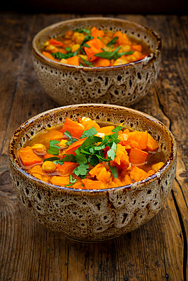 Two bowls of spicy oriental pumpkin stew with chick-peas, parsley and Hokkaido squash - p300m2156472 by Larissa Veronesi