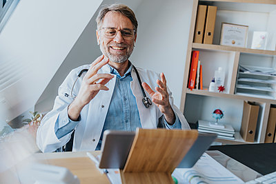 Male doctor gesturing while talking on video call over digital tablet at doctor's office - p300m2267719 by Mareen Fischinger