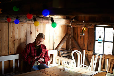 Young woman using smart phone while sitting at table in log cabin - p426m2118372 by Maskot