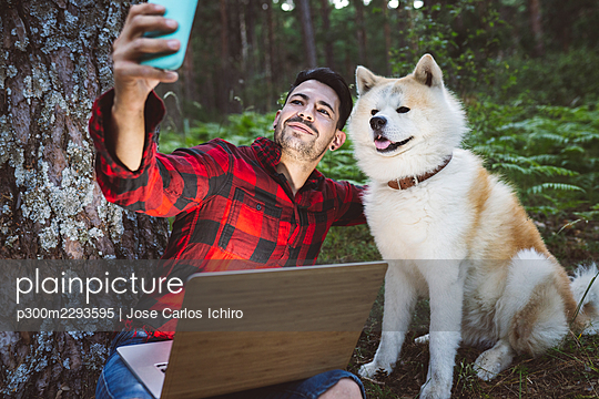 Man taking selfie with dog through mobile phone while sitting at forest - p300m2293595 by Jose Carlos Ichiro