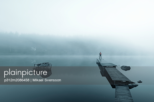 Man on pier in lake in morning fog - p312m2086458 by Mikael Svensson