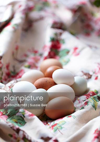 Brown and white hens eggs on a floral cloth - p349m2167883 by Sussie Bell