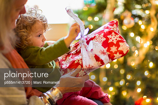 Caucasian grandmother and grandson opening presents near Christmas tree - p555m1413720 by Marc Romanelli