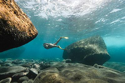 Full length of woman diving undersea - p1166m2067144 by Cavan Images