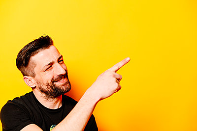 Man in front of a yellow background pointing with his pointing finger, portrait - p1267m2272512 by Jörg Meier