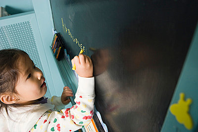 Girl writing on a blackboard - p9248483f by Image Source