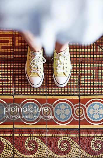 Woman wearing yellow sneakers standing on mosaic floor, partial view - p300m2012191 von gpointstudio