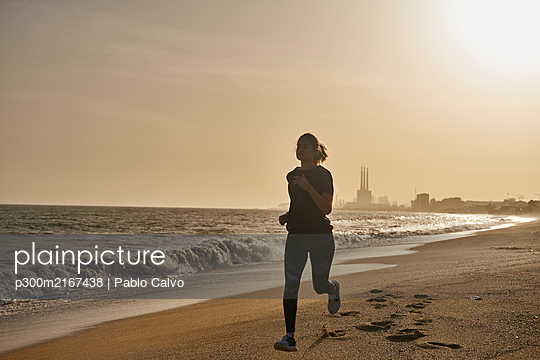 Young woman running on the beach at sunset - p300m2167438 by Pablo Calvo