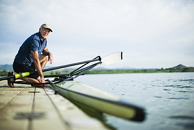 A middle-aged man on a jetty preparing a rowing boat for an outing.  - p1100m876294f by Jamie Kripke