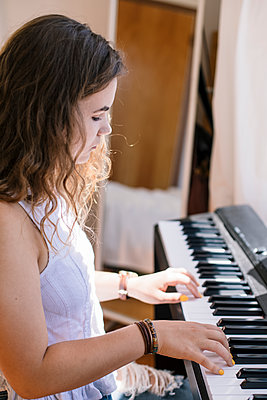 Side view girl playing piano in bedroom - p1166m2192019 by Cavan Images