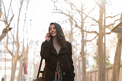 Smiling young woman on the phone in the city - p300m2166188 by VITTA GALLERY