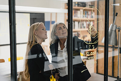 Mature and young businesswoman looking at chart on glass pane in office - p300m2171024 by Gustafsson