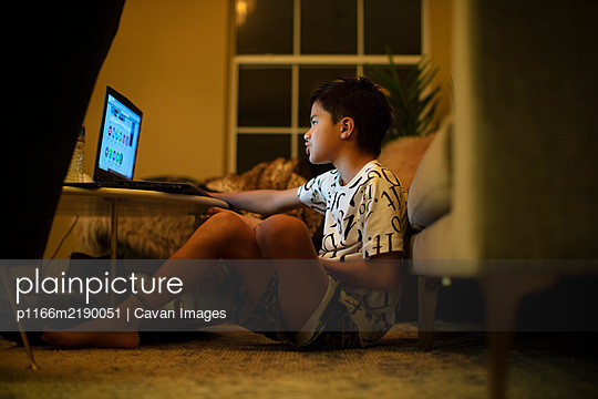 A half Japanese boy uses a laptop in the living room - p1166m2190051 by Cavan Images