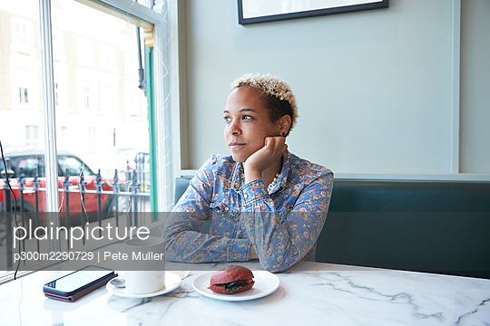 Thoughtful mid adult woman looking away sitting in cafe - p300m2290729 by Pete Muller