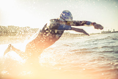 A swimmer in a wet suit running into the water, making a splash.  - p1100m1112331f by Mint Images