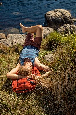 Junger Mann macht eine Pause beim Wandern - p1355m1574234 von Tomasrodriguez