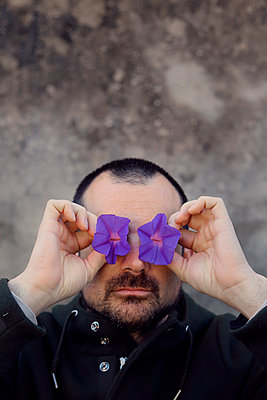Man with purple flowers in front of eyes - p1521m2150068 by Charlotte Zobel