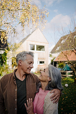 Happy senior couple in garden of their home in autumn - p300m2155009 by Gustafsson