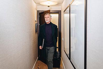 Mature businessman with laptop entering in hotel room - p300m2273796 by Daniel González