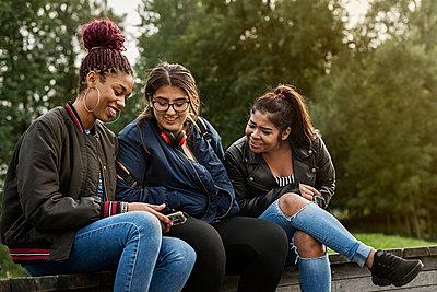 Teenage girls using smart phone - p352m2120981 by Folio Images