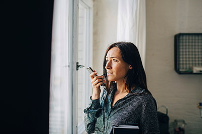 Creative businesswoman talking on smart phone while standing by window in office - p426m2045988 by Maskot