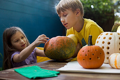 Boy and sister preparing pumpkins on garden table - p924m1468908 by Kinzie Riehm