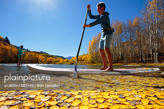 A woman and man enjoy the fall bliss while paddle boarding on an inflatable SUP boards near Telluride, Colorado in autumn in the San Juan Mountains.                       - p1460m1583149 by Ben Herndon