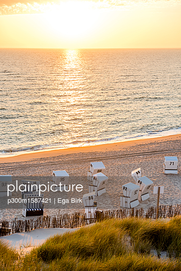Germany, Schleswig-Holstein, Sylt, beach and empty hooded beach chairs at sunset - p300m1587421 von Ega Birk