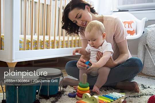 Caucasian mother and baby son playing with toys on floor - p555m1303864 by JGI/Jamie Grill
