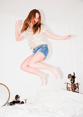 Junge Frau springt auf dem Bett - p1008m1169083 von Valerie Schmidt