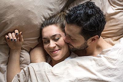 Glückliches junges Paar liegt im Bett und kuschelt  - p1301m1424742 von Delia Baum