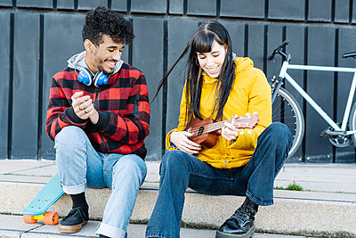Smiling woman playing guitar while sitting by male friend on footpath - p300m2242957 by COROIMAGE