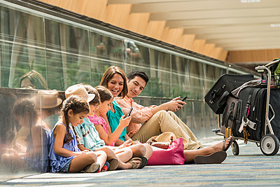Family waiting on floor of airport using cell phones - p555m1490968 by Mark Edward Atkinson/Tracey Lee