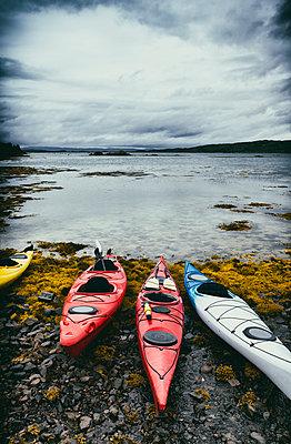 Ocean canoes on stony beach seascape coast seaweed nobody - p609m2066443 by WALSH photography
