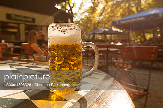 Beer mug on table in beer garden at evening twilight - p300m1506328 by Christina Falkenberg