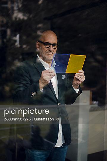 Senior architect standing at window, choosing materials - p300m1587276 von Gustafsson