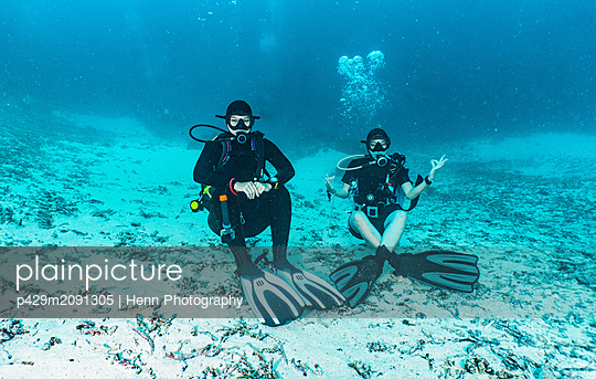 Underwater view of two divers waiting at the bottom of the ocean, portrait,  Raja Ampat, Sorong, Nusa Tenggara Barat, Indonesia - p429m2091305 by Henn Photography