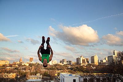 Full length of man jumping upside down against sky in city - p1166m1423123 by Cavan Images