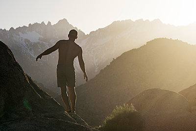 Rear view of hiker balancing on mountain against dawn sky - p1166m1473849 by Cavan Images