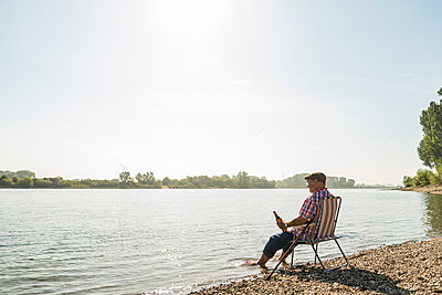Germany, Ludwigshafen, senior man with beer bottle sitting on folding chair at riverside - p300m1068897f by Uwe Umstätter