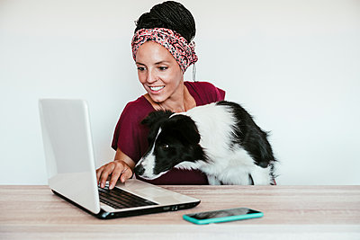 Female freelancer with Border Collie using laptop on table at home office - p300m2251131 by Eva Blanco