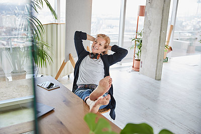 Smiling businesswoman looking away while sitting with feet up on desk at home - p300m2266031 by Jo Kirchherr