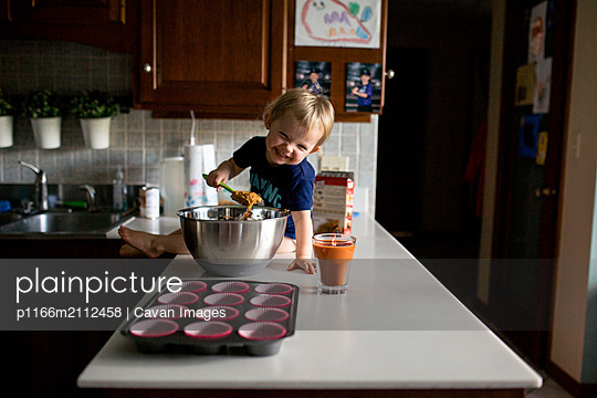 Happy toddler girl sitting on counter helping bake muffins - p1166m2112458 by Cavan Images