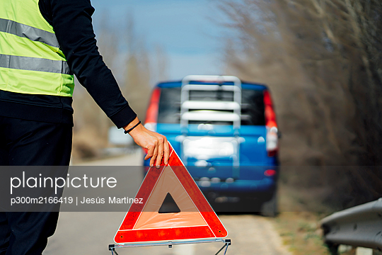Man putting warning triangle on country road by van breakdown - p300m2166419 by Jesús Martinez