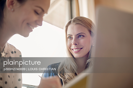 Business people using laptop while working together at office - p300m2240009 by LOUIS CHRISTIAN