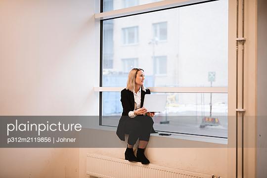 Businesswoman sitting on windowsill - p312m2119856 by Johner