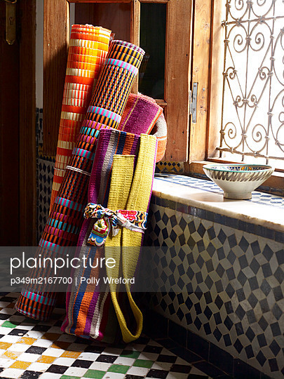 Rolls of fabric and geometric tiling in Moroccan riad, North Africa - p349m2167700 by Polly Wreford