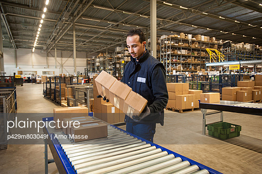 Male warehouse worker selecting cardboard boxes from conveyor belt - p429m803049f by Arno Masse