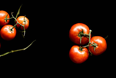Red tomatoes on black background - p1166m2094538 by Cavan Images
